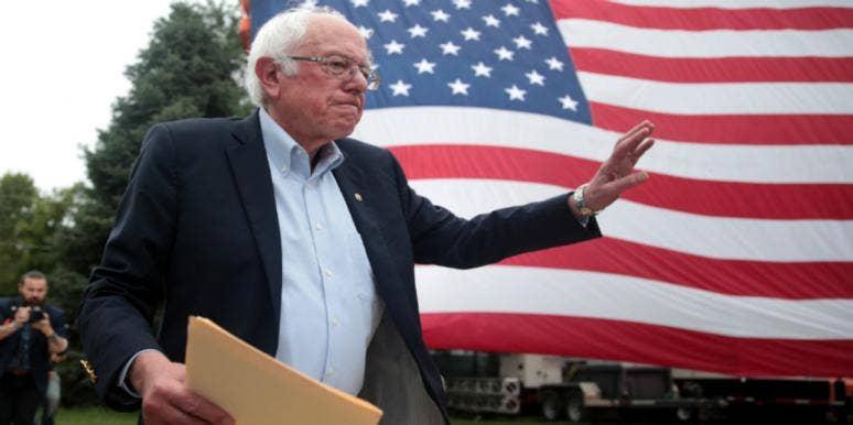 bernie sanders holding envelope in front of american flag