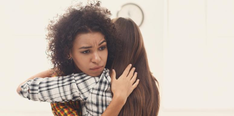 unhappy woman hugging another woman