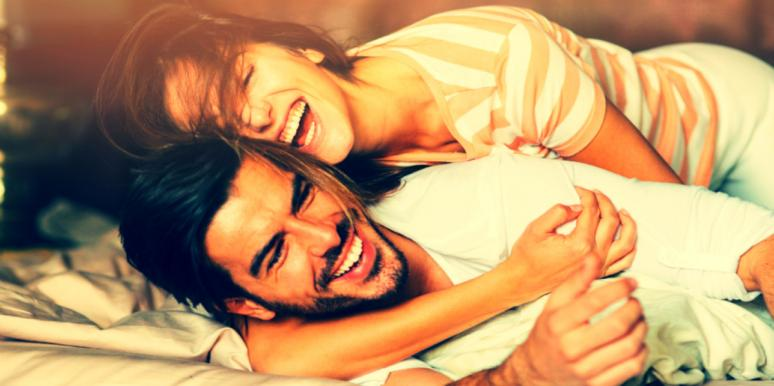 couple smiling and laughing holding each other in bed