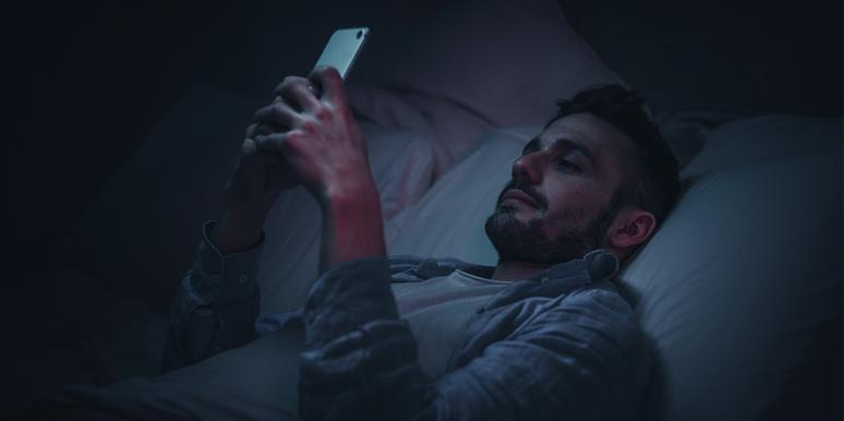 man laying in bed at night looking at phone