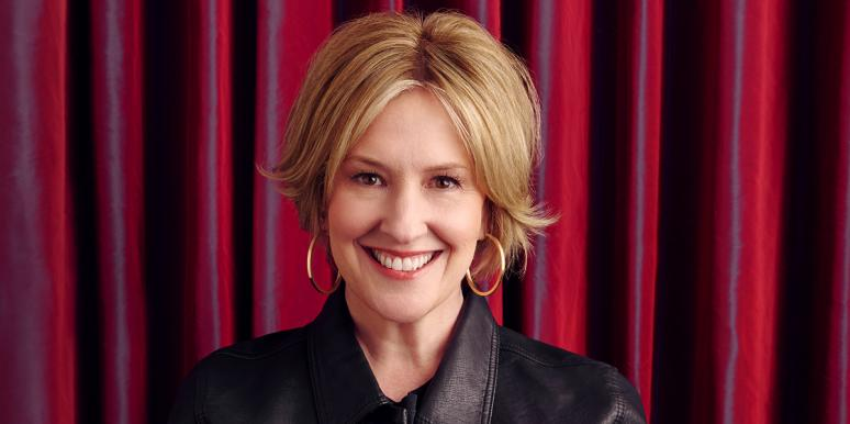 Headshot of Brené Brown looking sassy in front of a red backdrop