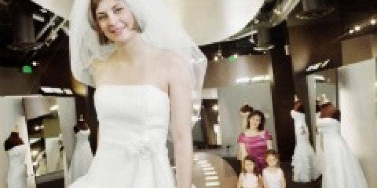 woman trying on wedding dress