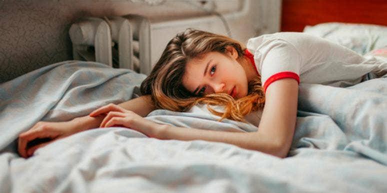 woman awake in bed hugging covers looking sad
