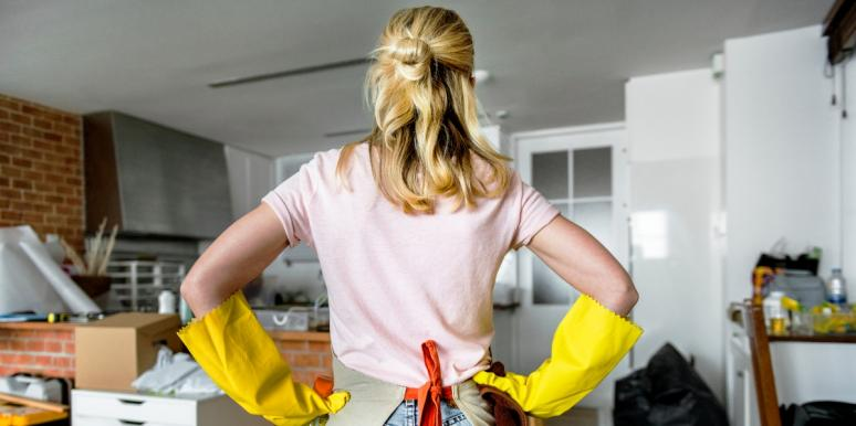 woman with hands on hips looking at messy house
