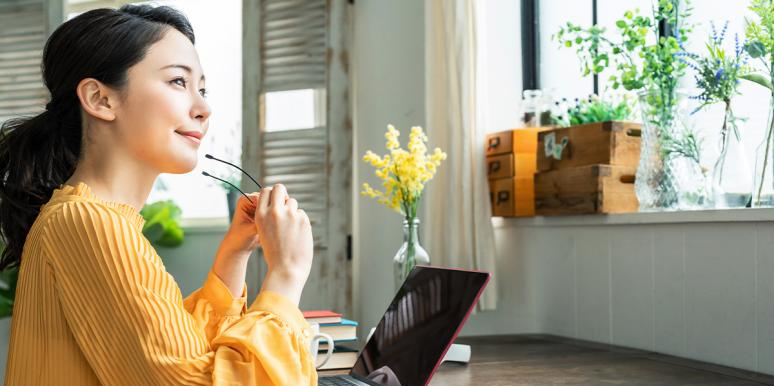 woman putting on glasses in front of laptop