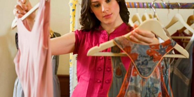 woman selecting outfit from closet clothes hangers