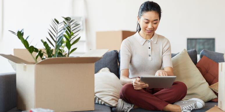 woman sitting with ipad and box with plant
