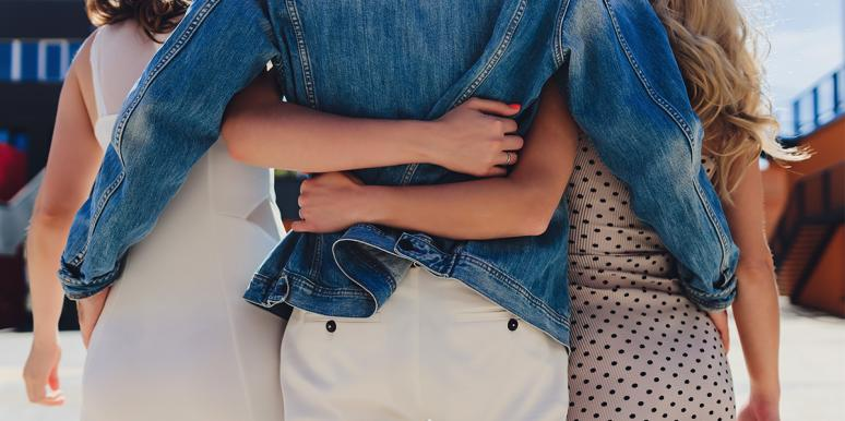 polyamorous couple arms wrapped around back of waist