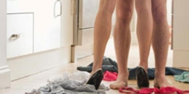 couple's naked legs in kitchen