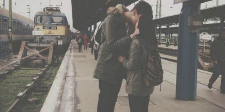 couple kissing next to train