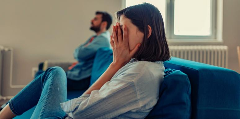 upset woman sitting on the couch with man