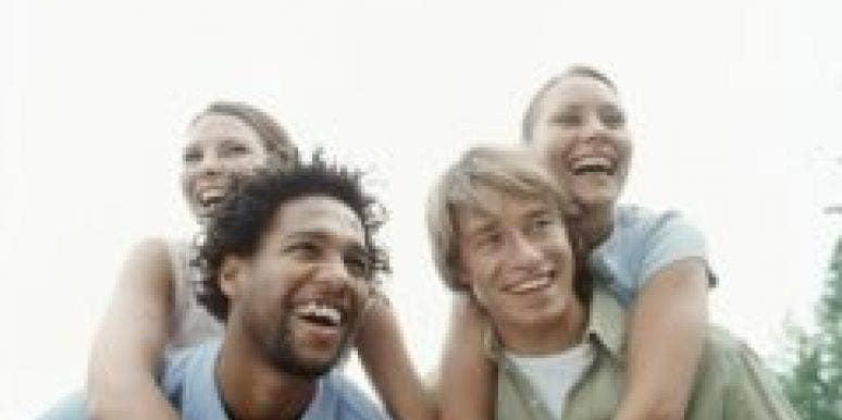 couples piggy back laughing black caucasian outside