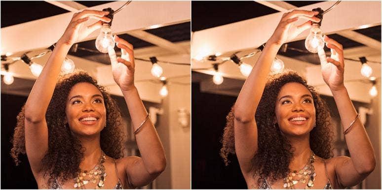 happy woman fixing a lightbulb