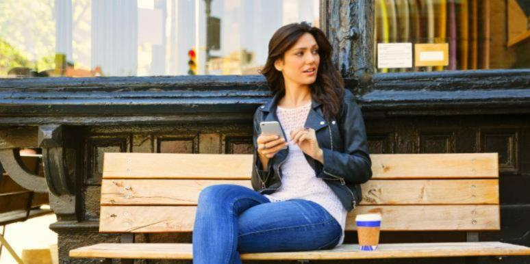 woman sitting on a bench with her phone