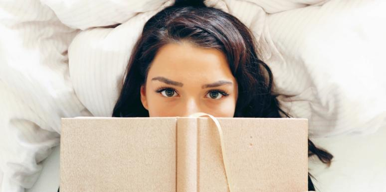 woman lying on bed with book over her face