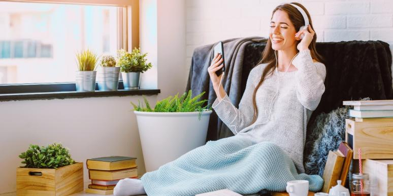 woman wearing headphones covered in blanket at home