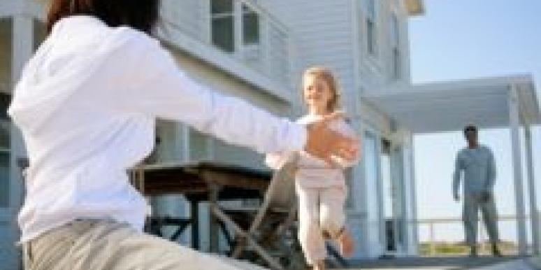 daughter running into arms of mother father looking on