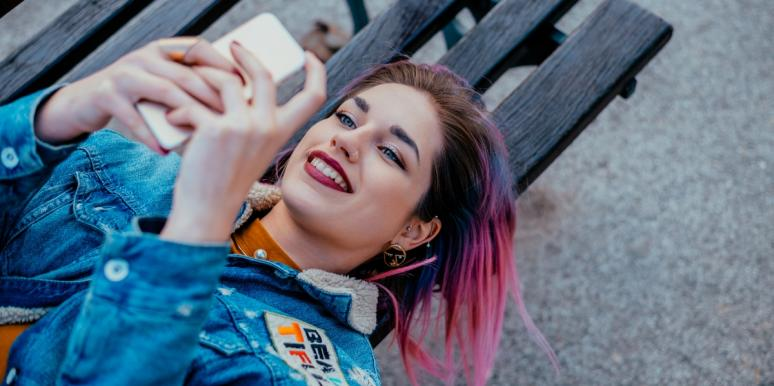 pink-haired woman lying on bench texting