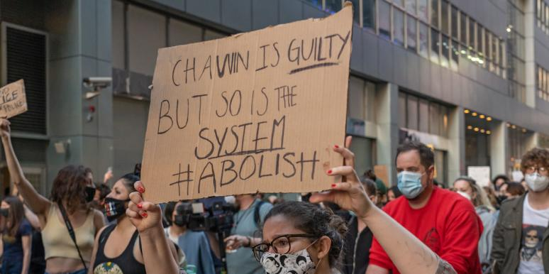 Woman holding sign that says Chauvin is guilty, but so is the system