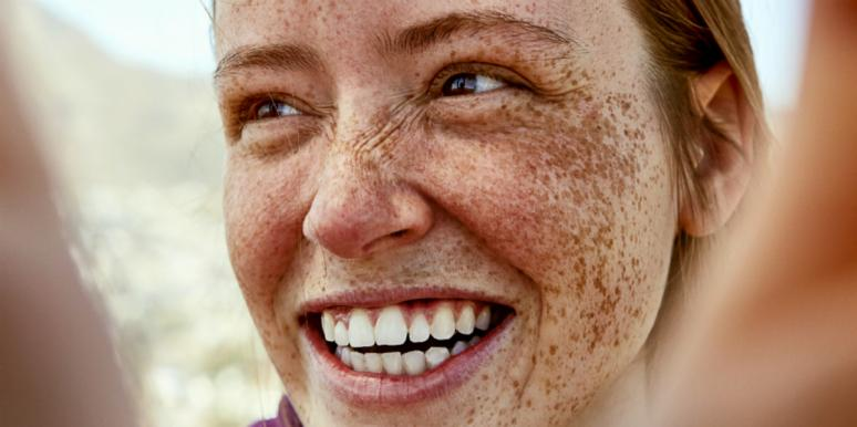 woman with freckles smiling wide showing teeth