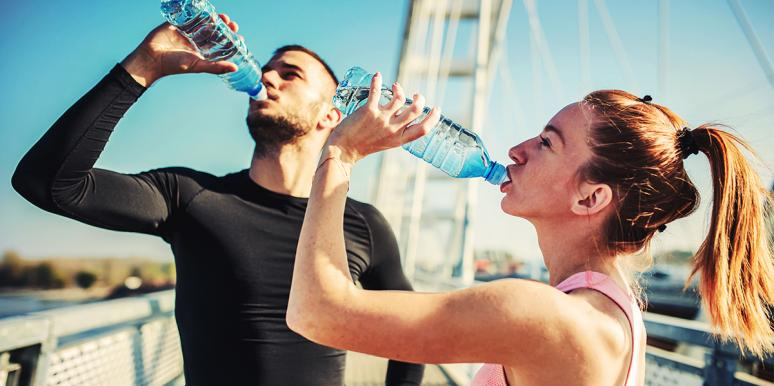 man and woman drinking water from bottles