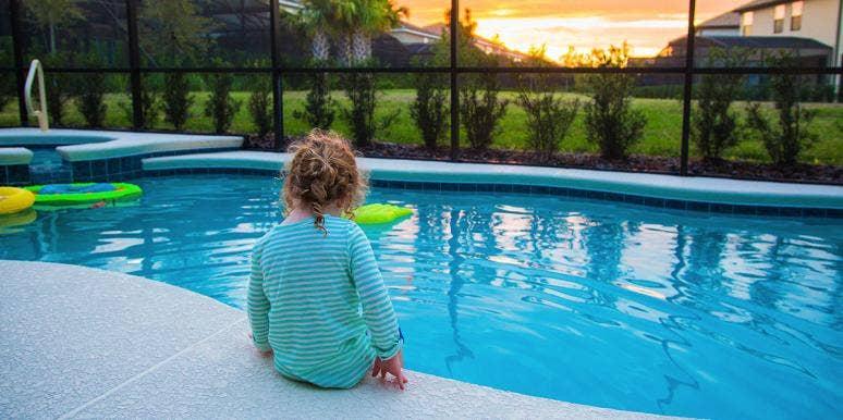 toddler sitting by swinning pool