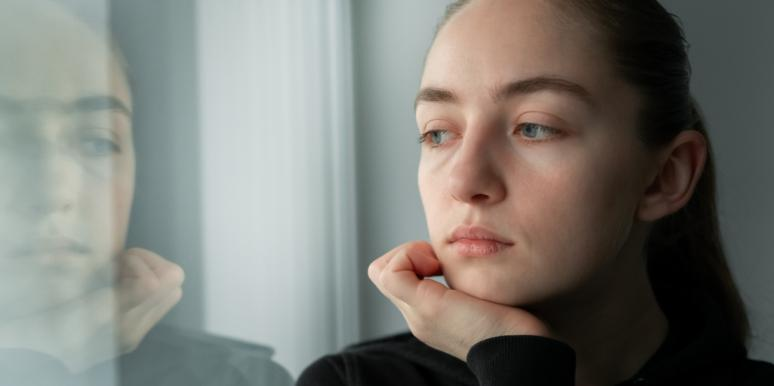 sad woman looking in window at reflection