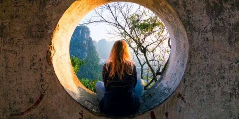 woman in tunnel facing away meditating