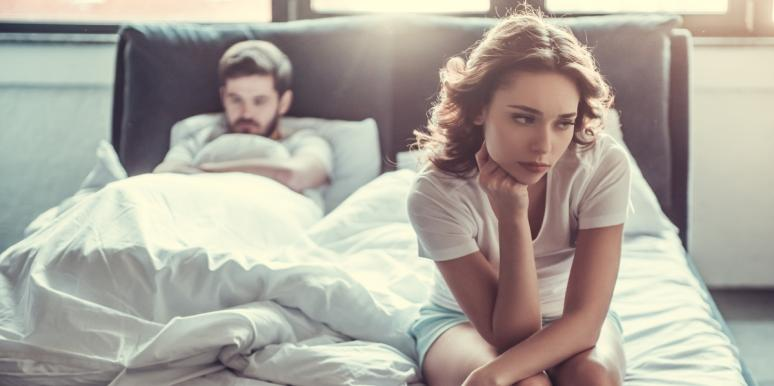 sad woman sitting at the end of bed after sex