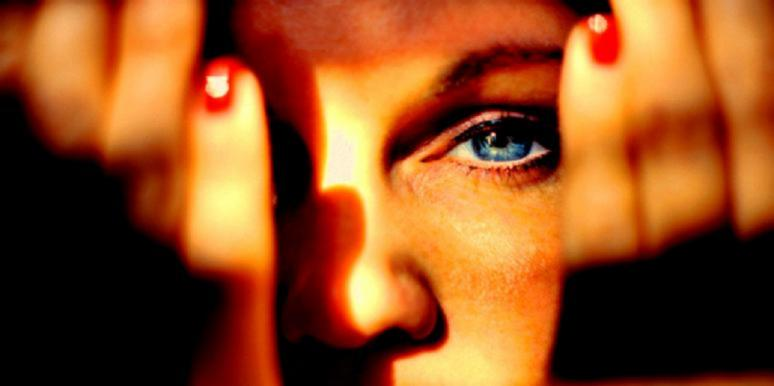 woman with hands in front of face showing her eye