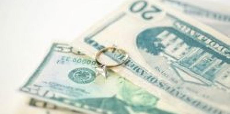 engagement ring resting on pile of money