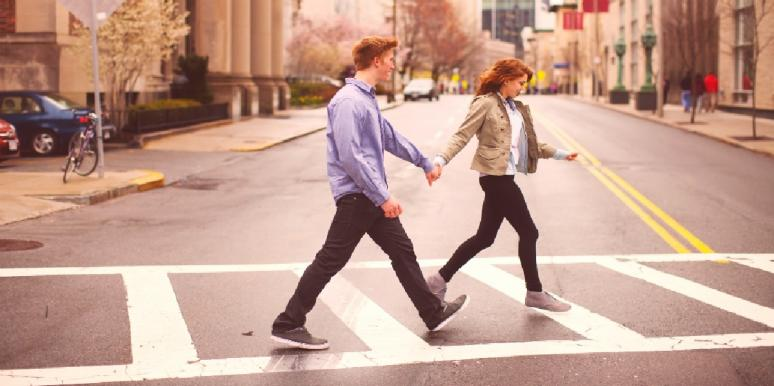 man holding woman's hand crossing the street