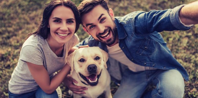 couple posing for a selfie with dog