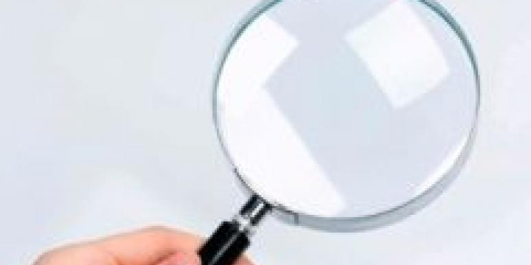 female hand holding magnifying glass