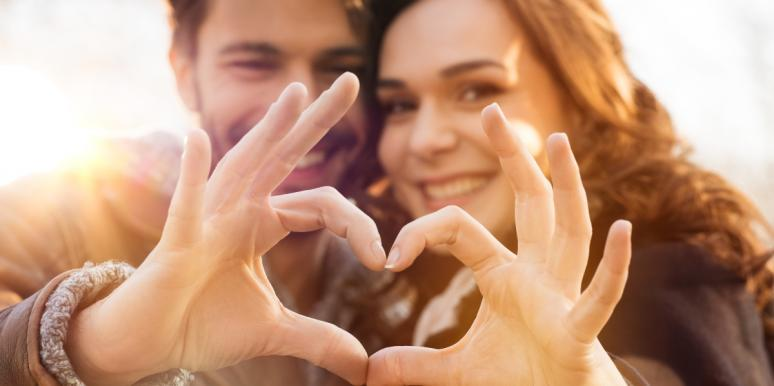 man and woman forming a heart with hands