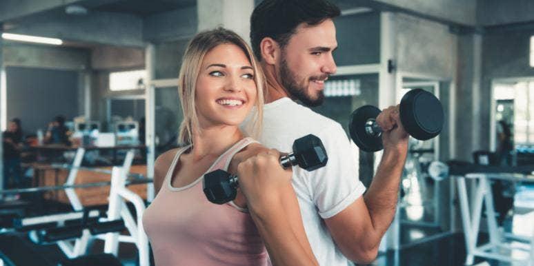 man and woman lifting weights at gym smiling