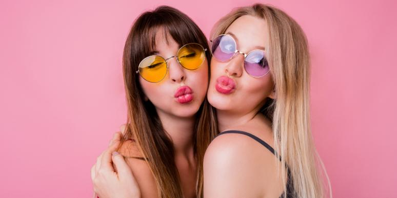 two friends making kissy faces pink background