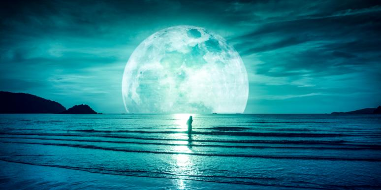 woman standing in front of a moon by water