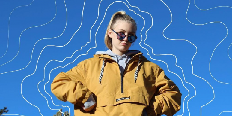 Gabby Petito in a yellow pullover in front of a blue sky
