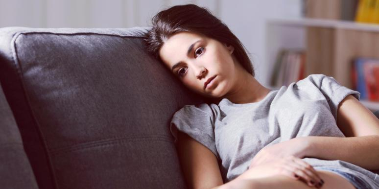 sad-looking woman sitting on couch