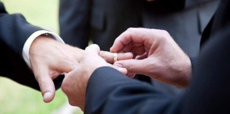 man placing ring on man's finger
