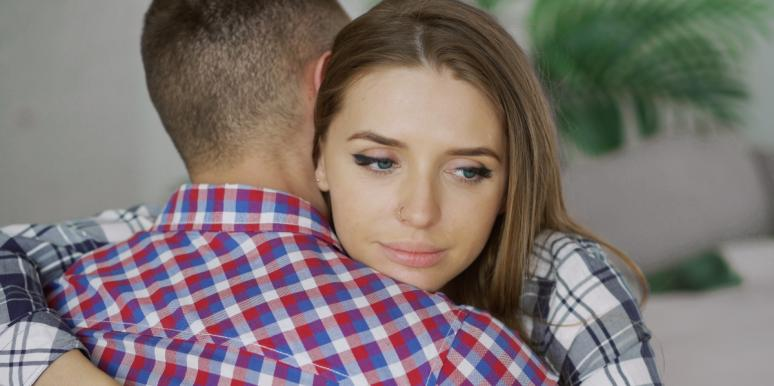 sad looking woman hugging man