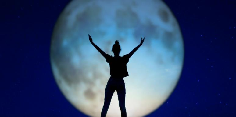 woman standing in front of full moon with arms open