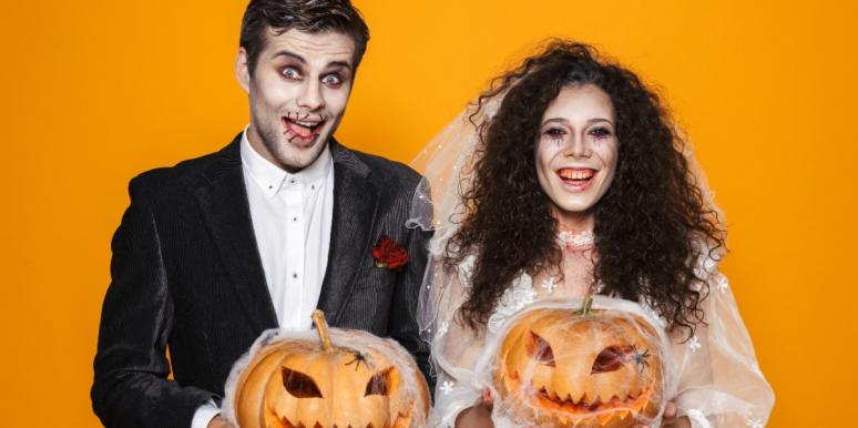 couple in halloween wedding attire holding pumpkins