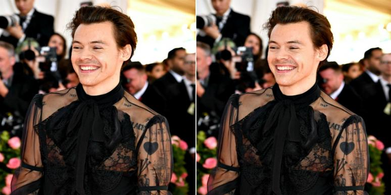 Harry Styles wears a lacy black top, his tattoos showing through
