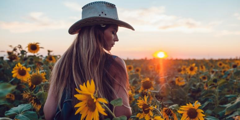 woman at sunset surrounded by sunflowers