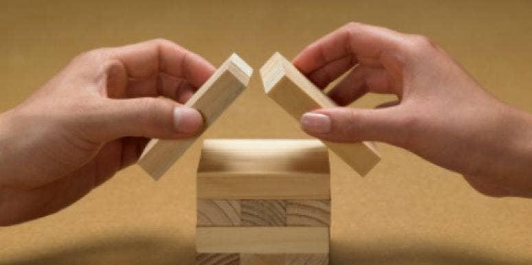 couples hands building blocks house