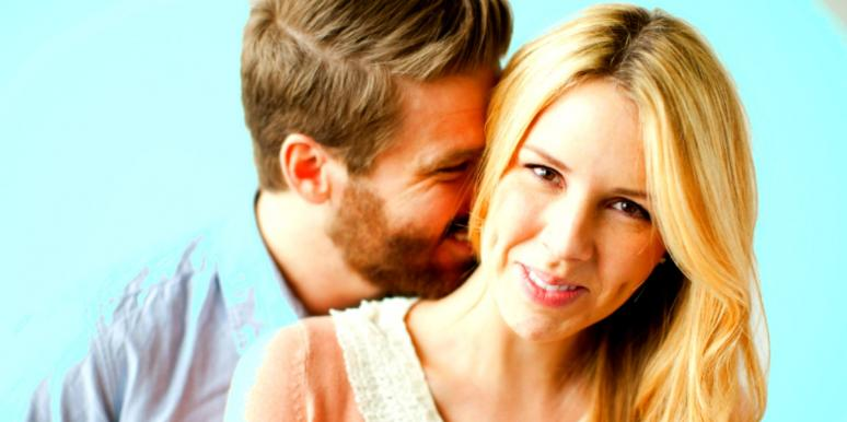 man kissing woman's neck woman smiling blue background