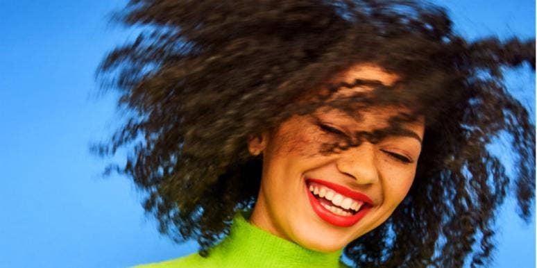 woman in green turtleneck smiling