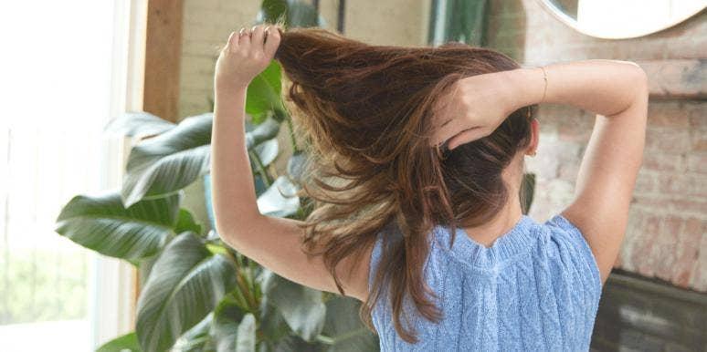 woman pulling long hair behind head